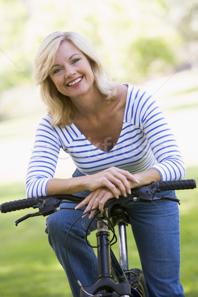Stock photo: Woman on bike outdoors smiling