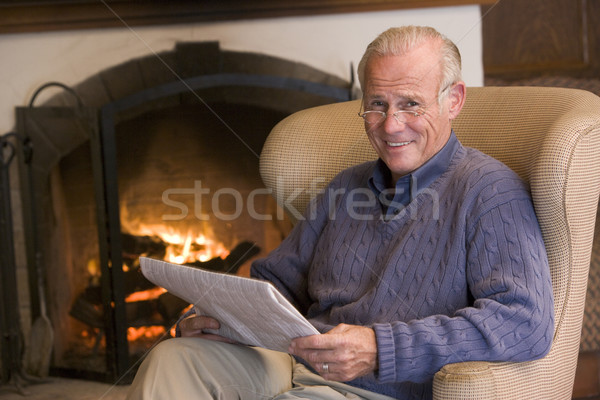 Man sitting in living room by fireplace with newspaper smiling Stock photo © monkey_business