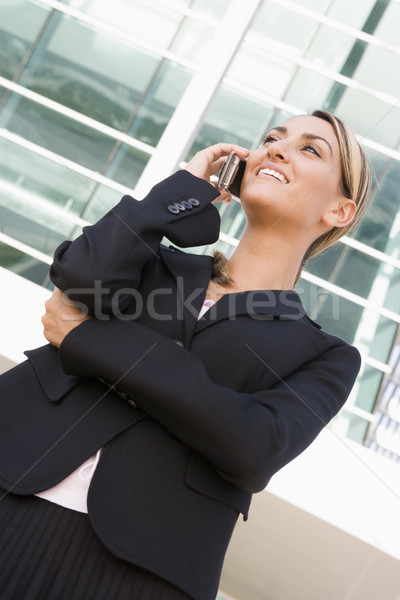 Businesswoman standing outdoors using cellular phone and smiling Stock photo © monkey_business