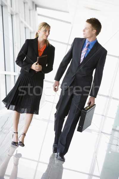 Two businesspeople walking in corridor talking Stock photo © monkey_business
