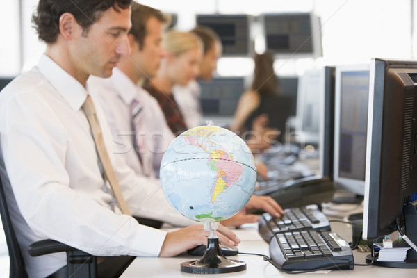 Five businesspeople in office space with a desk globe in foregro Stock photo © monkey_business