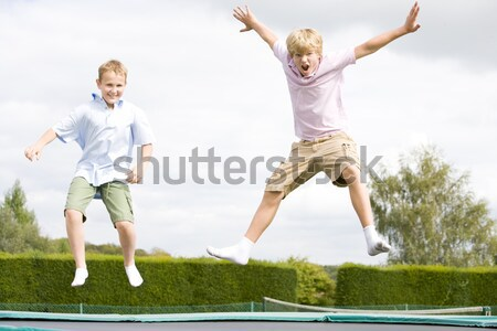 Two young girls jumping on trampoline smiling Stock photo © monkey_business