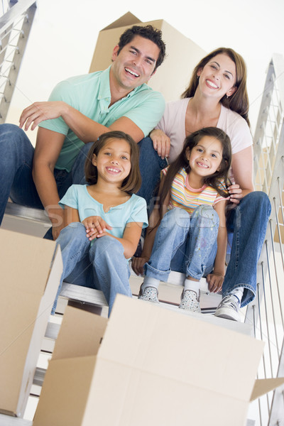 Family sitting on staircase with boxes in new home smiling Stock photo © monkey_business