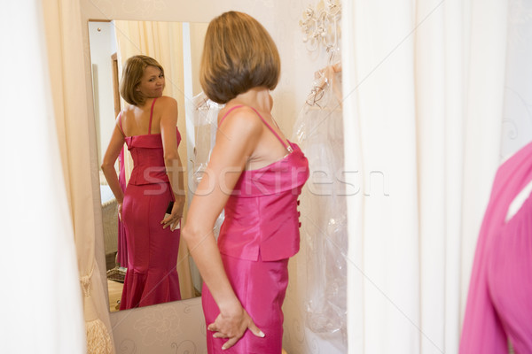 Woman trying on dresses and frowning Stock photo © monkey_business