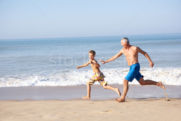 Grandfather chasing young boy on beach Stock photo © monkey_business