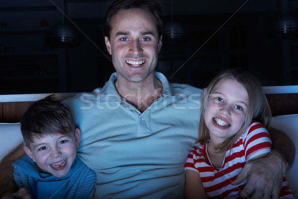Father And Children Watching Programme On TV Sitting On Sofa Tog Stock photo © monkey_business