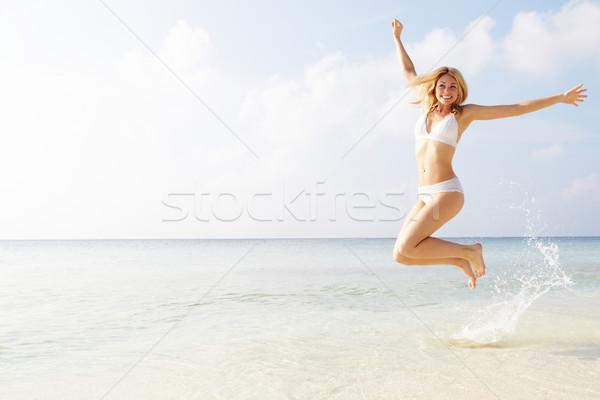 Nő ugrik levegő trópusi tengerpart tengerpart tenger Stock fotó © monkey_business
