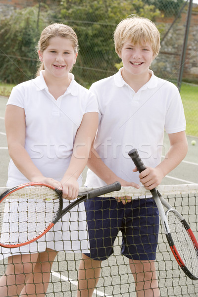 Two young friends with rackets on tennis court smiling Stock photo © monkey_business