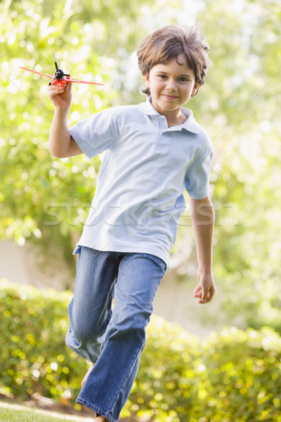 Young boy with toy airplane running outdoors smiling Stock photo © monkey_business