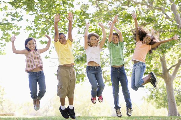 Cinque giovani amici jumping esterna sorridere Foto d'archivio © monkey_business