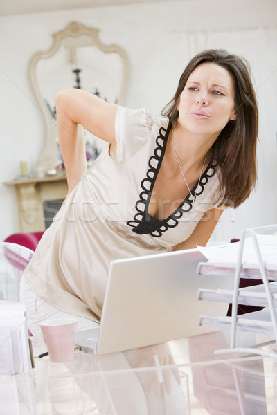 Pregnant woman in home office with a sore back Stock photo © monkey_business