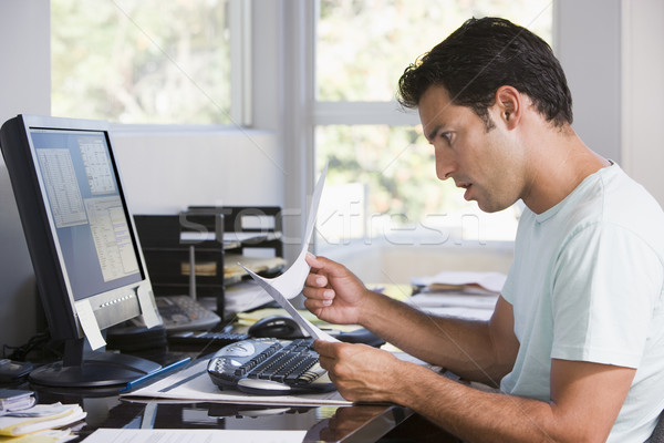 Man in home office using computer holding paperwork and looking  Stock photo © monkey_business
