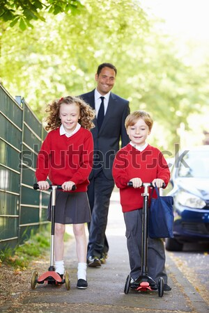 A woman with a pushchair walking her son home from school Stock photo © monkey_business
