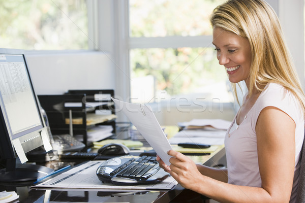 Woman in home office with computer and paperwork smiling Stock photo © monkey_business
