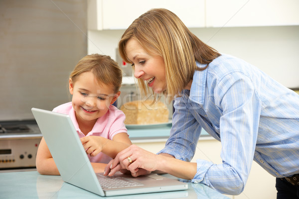 Mother and daughter using laptop in domestic kitchen Stock photo © monkey_business