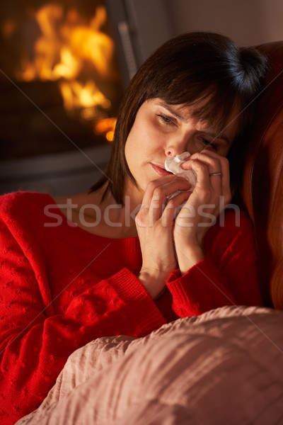 Sick Woman With Cold Resting On Sofa By Cosy Log Fire Stock photo © monkey_business