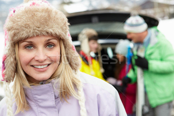 Mother Smiling At Camera Whilst Family Load Skis In Boot Of Car Stock photo © monkey_business