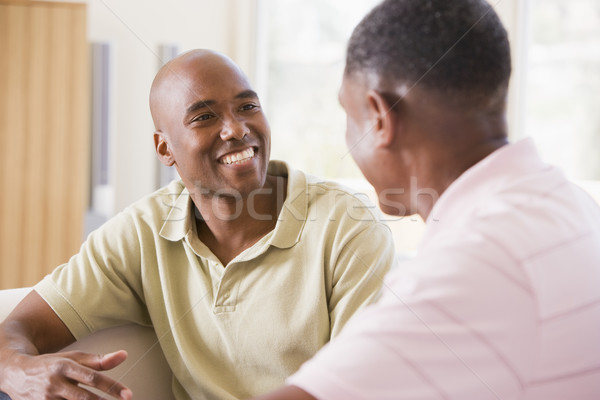 Two men in living room talking and smiling Stock photo © monkey_business