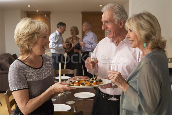 Woman Serving Hors D'oeuvres To Her Guests At A Dinner Party Stock photo © monkey_business