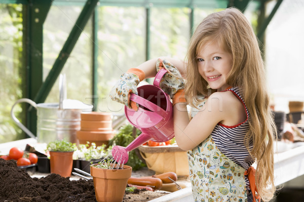 Jeune fille effet de serre plante en pot souriant enfants Photo stock © monkey_business