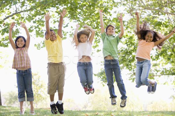 Stockfoto: Vijf · jonge · vrienden · springen · buitenshuis · glimlachend