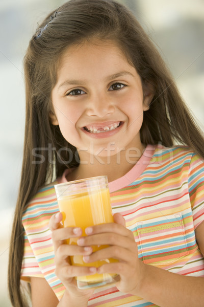 Young girl indoors drinking orange juice smiling Stock photo © monkey_business