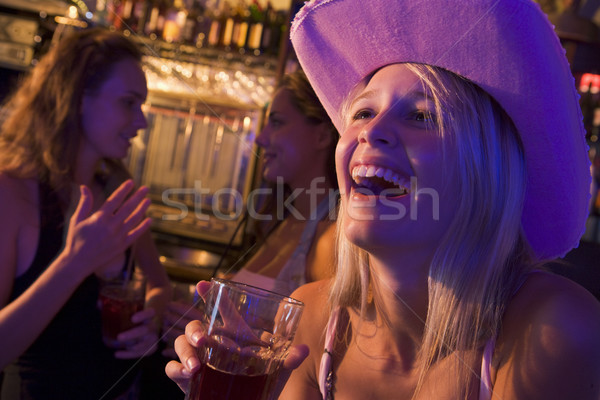 Stock photo: Young woman in cowboy hat laughing at a nightclub
