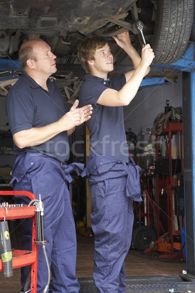 Stock photo: Mechanic and apprentice working on car