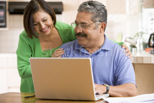 Couple in kitchen with laptop smiling Stock photo © monkey_business