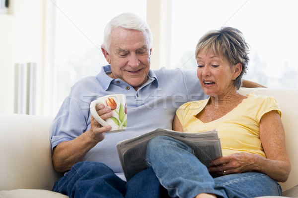 Stock photo: Couple in living room reading newspaper with coffee smiling