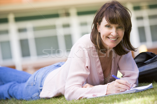 Stock photo: A woman writing notes while lying on a campus lawn