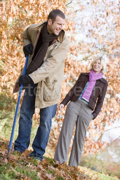 Couple raking up autumn leaves Stock photo © monkey_business