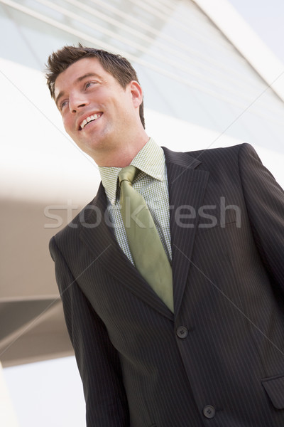 Businessman standing outdoors by building smiling Stock photo © monkey_business