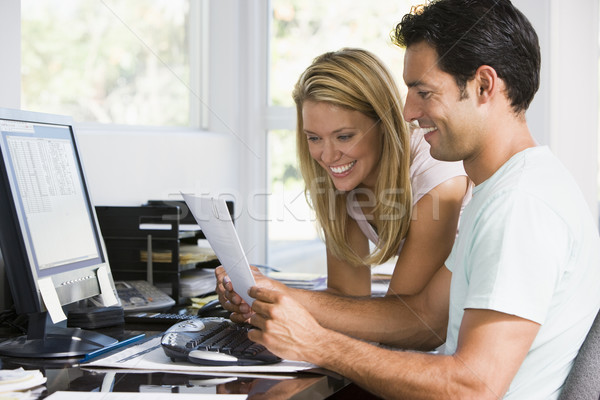 Stock photo: Couple in home office with computer and paperwork smiling