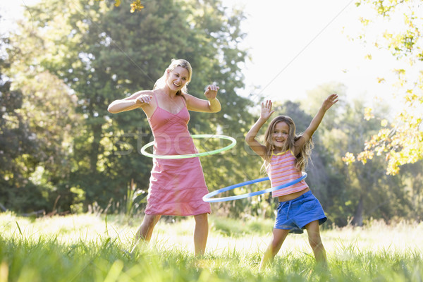 Woman and young girl outdoors using hula hoops and smiling Stock photo © monkey_business