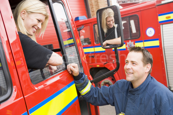 Firefighter sitting in the cab of a fire engine talking to a co- Stock photo © monkey_business