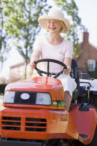 Woman outdoors driving lawnmower smiling Stock photo © monkey_business