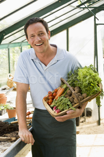 Man in greenhouse holding basket of vegetables smiling Stock photo © monkey_business