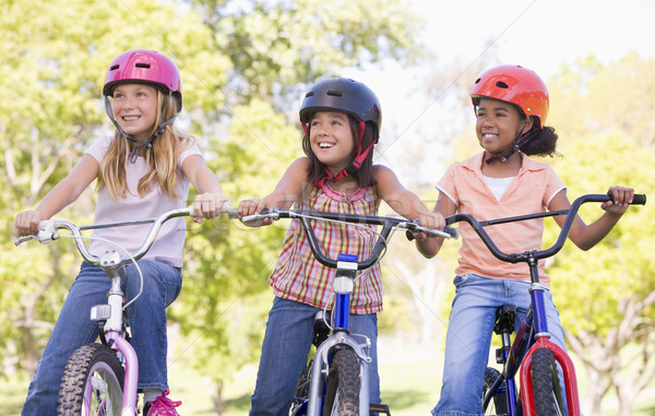 Three young girl friends outdoors on bicycles smiling Stock photo © monkey_business