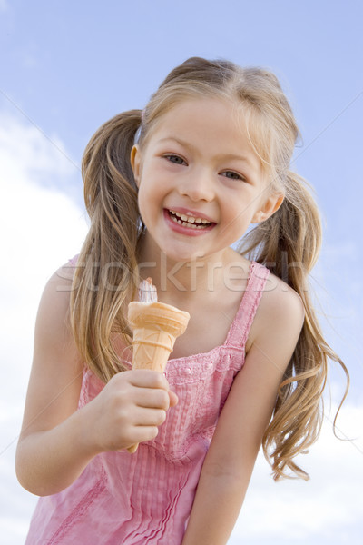 Young girl outdoors eating ice cream cone and smiling Stock photo © monkey_business
