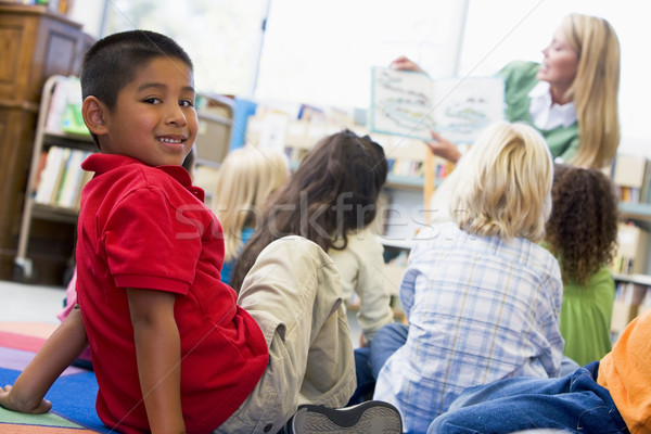 Kindergarten teacher reading to children in library, boy looking Stock photo © monkey_business