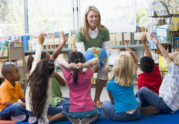 Kindergarten teacher and children with hands raised in library Stock photo © monkey_business
