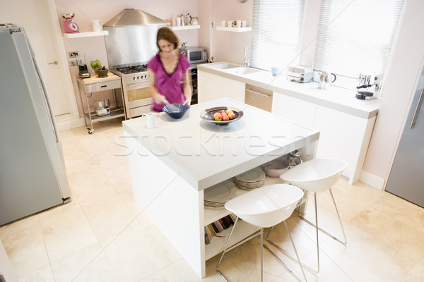 Woman in kitchen whisking on counter Stock photo © monkey_business