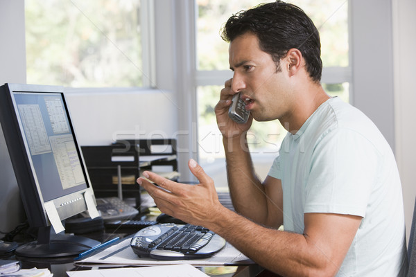 Man in home office on telephone using computer and frowning Stock photo © monkey_business