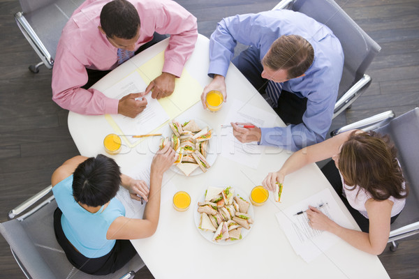Four businesspeople at boardroom table with sandwiches Stock photo © monkey_business