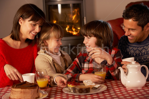 Portrait Of Family Enjoying Tea And Cake By Cosy Log Fire Stock photo © monkey_business
