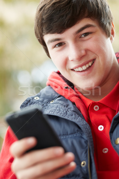 Teenage Boy Texting On Smartphone Wearing Winter Clothes Stock photo © monkey_business