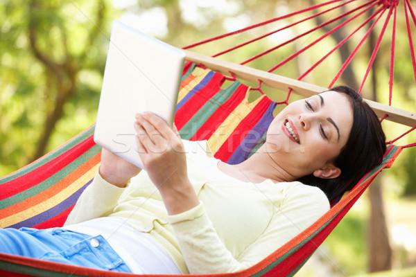 Mujer relajante hamaca ebook mujeres feliz Foto stock © monkey_business