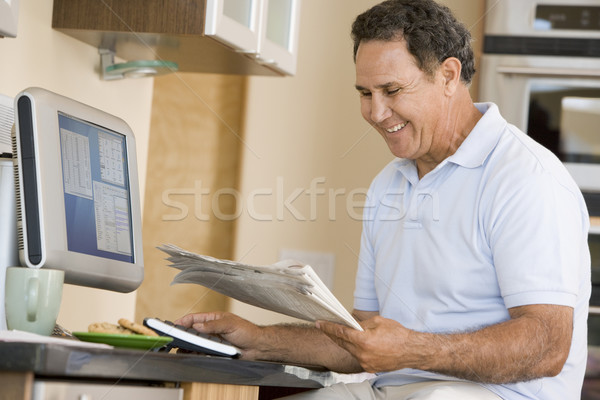 Man in kitchen with computer and newspaper smiling Stock photo © monkey_business