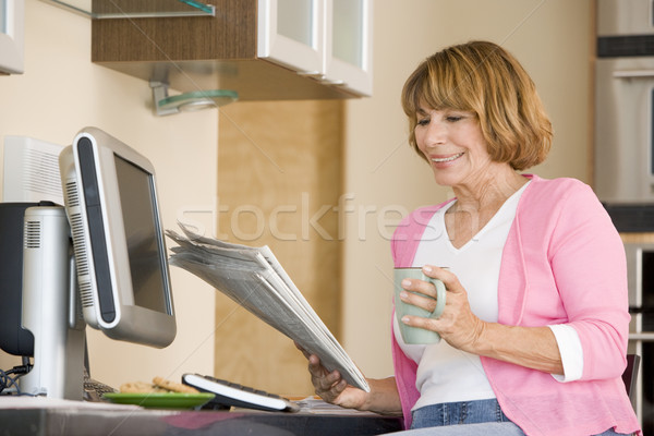 Woman in kitchen with newspaper and coffee smiling Stock photo © monkey_business